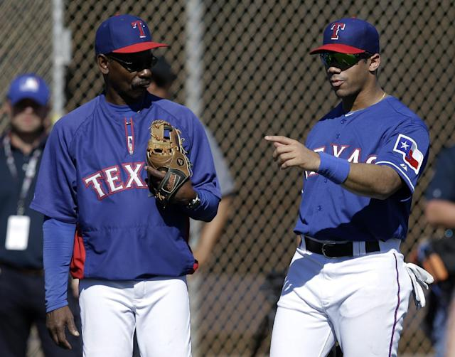 Seattle Seahawks quarterback Russell Wilson, right, talks with Texas Rangers manager Ron Washington on a practice field as the team takes batting practice during spring training baseball practice, Monday, March 3, 2014, in Surprise, Ariz. (AP Photo/Tony Gutierrez)