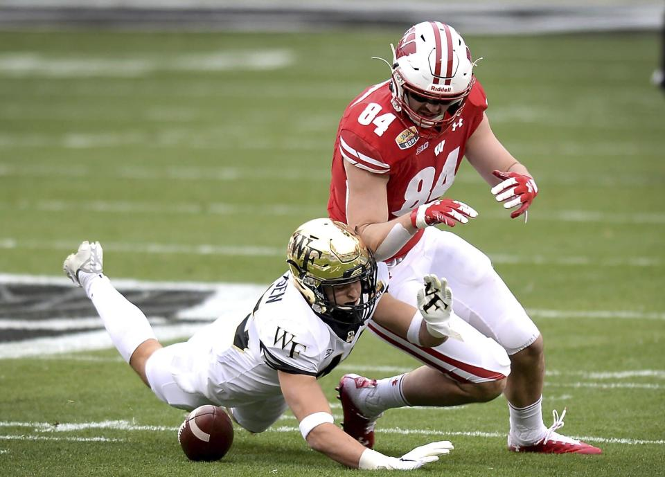 Wake Forest linebacker Nick Andersen, left, breaks up a pass meant for Wisconsin tight end Jake Ferguson, right, during the first quarter of the Duke's Mayo Bowl NCAA college football game at Bank of America Stadium in Charlotte, N.C., Wednesday, Dec. 30, 2020. (Jeff Siner/The News & Observer via AP)