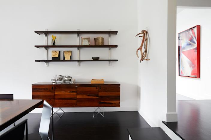"<div class=""caption""> This corner of the dining room showcases two of Brazil's midcentury design icons: Sergio Rodrigues and Jorge Zalszupin, who produced a series of geometrically shaped furnishings in jacarandá, a richly veined local rosewood that has since become endangered. The sideboard with thin metal legs is by Zalszupin, and the wall-mounted ""George Nelson"" shelves are by Rodrigues. Both were designed and built in the 1960s. The wall sculpture on the right, a wax–and–epoxy resin piece called <em>Romeo, My Deer</em>, is by Belgian artist Berlinde de Bruyckere. </div>"