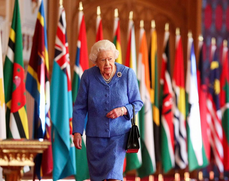 Britain's Queen Elizabeth II walks past Commonwealth flags in St George's Hall at Windsor Castle, England to mark Commonwealth Day in this image issued on Saturday March 6, 2021.