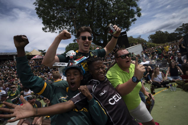 South Africa fans celebrate their team scoring at the Pirates Rugby Club in Johannesburg, South Africa, as they watch the Rugby World Cup final between South Africa and England being played in Tokyo, Japan on Saturday Nov. 2, 2019. (AP Photo/Jerome Delay)