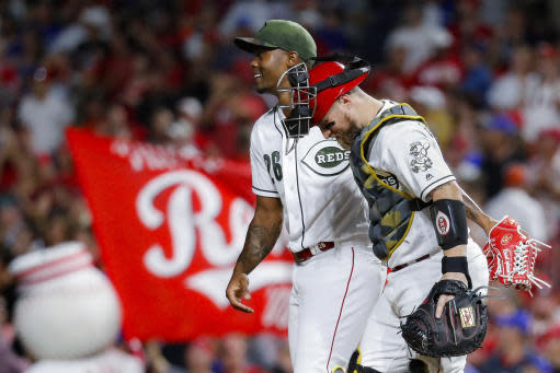 Cincinnati Reds relief pitcher Raisel Iglesias (26) celebrates with catcher Tucker Barnhart, right, after closing the ninth inning of a baseball game against the Chicago Cubs, Friday, Aug. 9, 2019, in Cincinnati. (AP Photo/John Minchillo)