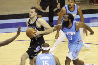 Houston Rockets guard James Harden reaches in against Sacramento Kings Nemanja Bjelica who goes to the basket during the first half of an NBA basketball game Thursday Dec. 31, 2020, in Houston. (AP Photo/Richard Carson)