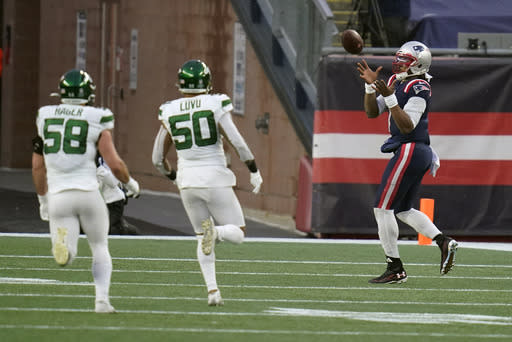 New England Patriots quarterback Cam Newton, right, catches a touchdown pass thrown by wide receiver Jakobi Meyers, as New York Jets defenders Bryce Hager, left, and Frankie Luvu give chase in the second half of an NFL football game, Sunday, Jan. 3, 2021, in Foxborough, Mass. (AP Photo/Charles Krupa)