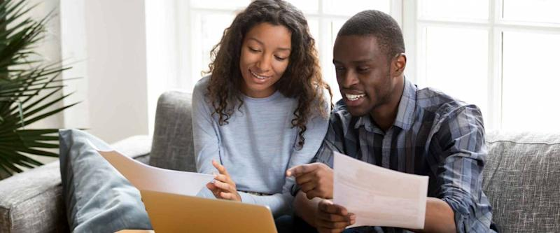 African black positive married couple sitting on sofa at home reviewing mortgage options
