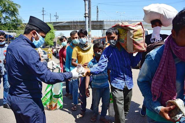 DELHI, INDIA - 2020/03/29: A man wearing a face mask as a preventive measure, distributes food to the migrant labourers and workers who are stranded on the border during the nationwide lock down. The Indian government imposed a 21 day nationwide lock down as a preventive measure against the corona virus pandemic. (Photo by Manish rajput/SOPA Images/LightRocket via Getty Images)