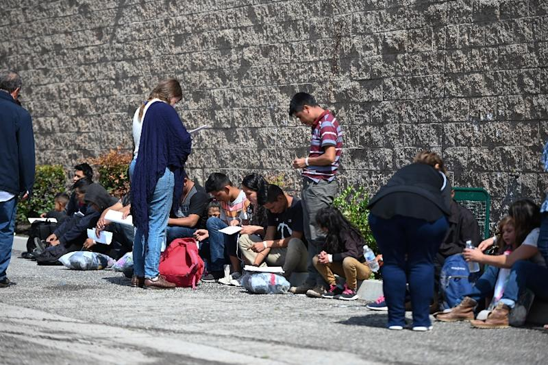 Volunteers assist Central American asylum seekers sitting outside the bus station in San Bernardino, California after they were brought there by US Border Patrol vans (AFP Photo/Robyn Beck)