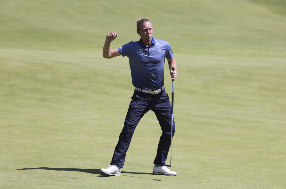 Germany's Marcel Siem celebrates after making a birdie putt on the 18th green during the second round of the British Open Golf Championship at Royal St George's golf course Sandwich, England, Friday, July 16, 2021. (AP Photo/Ian Walton)
