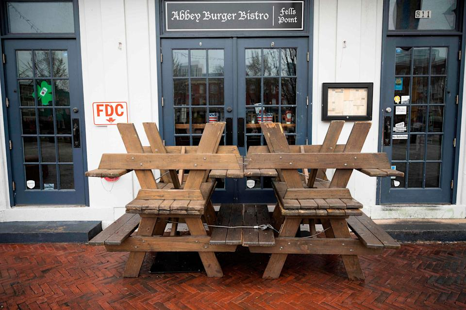 Picnic tables block the closed doors of Abbey Burger Bistro in Baltimore on March 19, 2020.