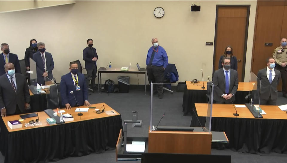 In this image from video, defense attorney Eric Nelson, and defendant, former Minneapolis police Officer Derek Chauvin, both on the right side of the courtroom, arrive for the verdict in Chauvin's trial for the 2020 death of George Floyd, Tuesday, April 20, 2021, at the Hennepin County Courthouse in Minneapolis, Minn. Behind the front table at left is prosecutor Jerry Blackwell, left, and Minnesota Attorney General Keith Ellison. Behind the rear table at left is prosecutor Steve Schleicher, left, and Assistant Minnesota Attorney General Matthew Frank. (Court TV via AP, Pool)