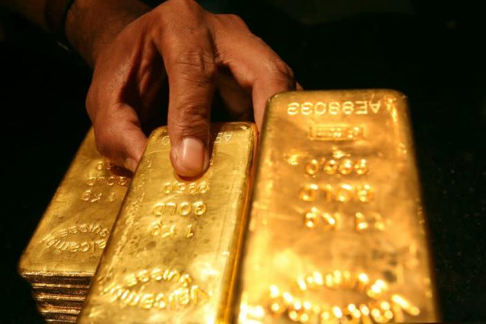 FILE PHOTO: A security guard places several one kilo gold bars inside a secured vault in Dubai April 20, 2006. S..