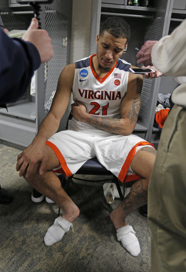 Virginia's Isaiah Wilkins (21) takes questions from the media in the locker room after the team's 74-54 loss to UMBC in a first-round game in the NCAA men's college basketball tournament in Charlotte, N.C., Friday, March 16, 2018. (AP Photo/Bob Leverone)