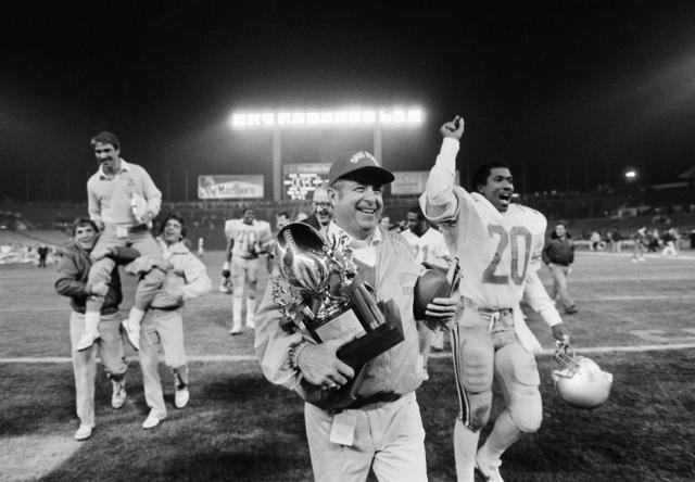 FILE - In this Dec. 18, 1982, file photo, Ohio State football coach Earle Bruce carries the trophy and game ball after his team defeated Brigham Young University 47-17 in the Holiday Bowl in San Diego, Calif. Bruce died in Columbus, Ohio at the age of 87, according to a statement released by his daughters through Ohio State on Friday. Hed been suffering from Alzheimers disease. (AP Photo/Lenny Ignelizi, File)