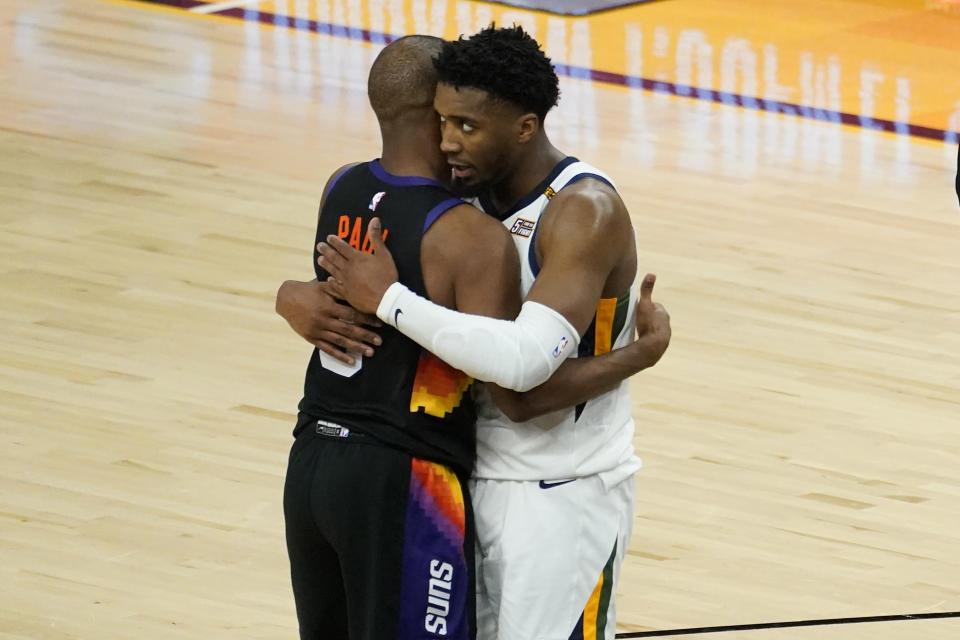 Phoenix Suns guard Chris Paul and Utah Jazz guard Donovan Mitchell, right, embrace after an NBA basketball game, Wednesday, April 7, 2021, in Phoenix. The Suns won 117-113 in overtime. (AP Photo/Matt York)