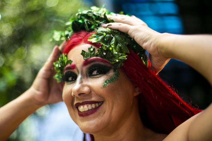 """A member of the """"Desliga da Justica"""" street band get dressed in her costume in Rio de Janeiro, Brazil, Sunday, Feb. 14, 2021. The group's performance was broadcast live on social media for those who were unable to participate in the carnival due to COVID restrictions after the city's government officially suspended Carnival and banned street parades or clandestine parties. (AP Photo/Bruna Prado)"""