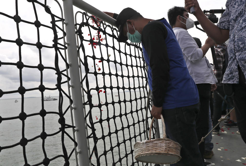 A relative sprinkle flowers into the Java Sea where Sriwijaya Air flight SJ-182 crashed on Jan. 9 killing all of its passengers, during a memorial ceremony held on deck of Indonesian Navy Ship KRI Semarang, near Jakarta in Indonesia, Friday, Jan. 22, 2021. (AP Photo/Tatan Syuflana)