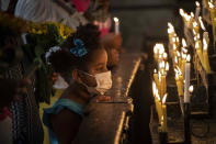 A girl wearing a face mask amid the COVID-19 pandemic kneels in prayer before candles at Our Lady of Cobre Church as faithful mark the feast day of Cuba's patron saint, the Virgin of Charity of Cobre, in Havana, Cuba, Wednesday, Sept. 8, 2021. For the second year in a row, the annual procession with the statue of the Virgin of Charity of Cobre was cancelled due to the pandemic. (AP Photo/Ramon Espinosa)