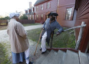 FILE - Historical interpreters Robert Watson Jr., talks with a fellow interpreter, Janice Canaday, left, at the Randolph house in Colonial Williamsburg in Williamsburg, Va., on Dec. 15, 2015. Colonial Williamsburg is an immersive living-history museum where costumed interpreters of history reenact scenes and portray figures from that period. (AP Photo/Steve Helber, File)