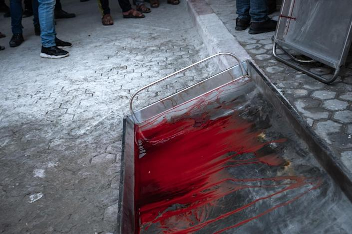 A metal pallet is covered with bright red blood