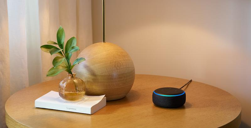 Echo Dot on a side table next to a lamp and a book