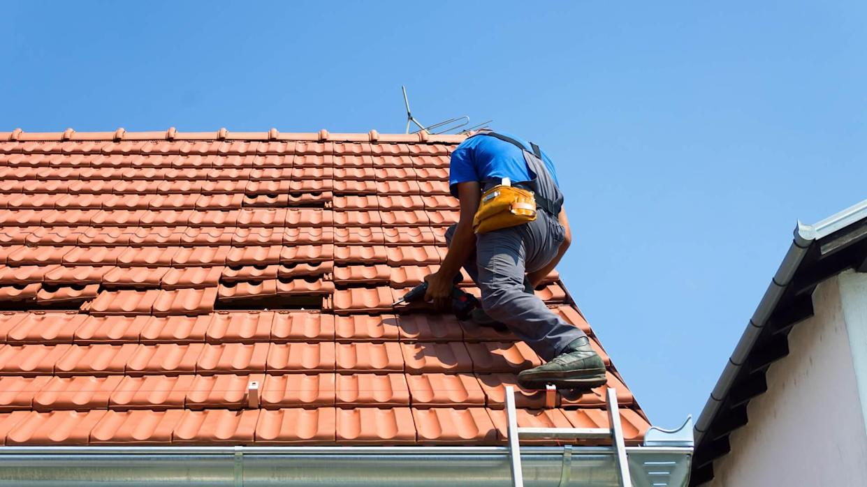 man fixing damaged terra cotta roof