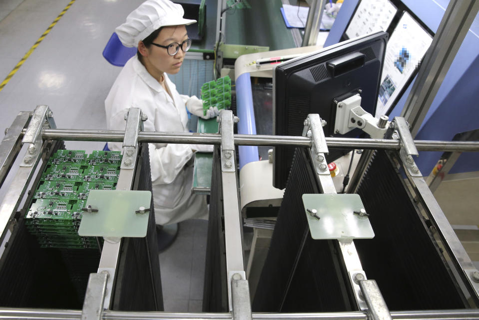 In this Aug. 27, 2019, photo, an employee works on the production line of a smart electricity meter manufacturing plant in Nantong in eastern China's Jiangsu province. Two surveys of Chinese manufacturing show demand is weak amid a mounting tariff war with Washington over trade and technology. (Chinatopix via AP)