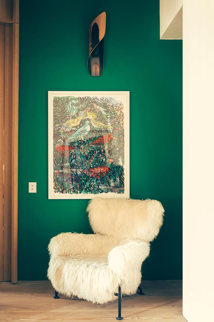 """<div class=""""caption""""> The green entrance in a Paris flat owned by designer François Champsaur is hung with a gouache by Portuguese artist Bela Silva. The armchair is Franco Albini for Cassina. The wall sconce was designed by Champsaur for Pouenat Ferronnier. </div>"""
