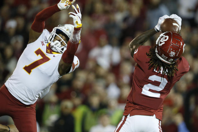 Oklahoma wide receiver CeeDee Lamb (2) catches a touchdown pass in front of Iowa State defensive back Justin Bickham (7) during the first quarter of an NCAA college football game in Norman, Okla., Saturday, Nov. 9, 2019. (AP Photo/Sue Ogrocki)