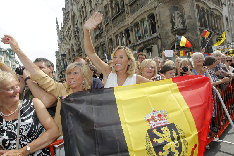 Fans of the Belgian Royals wave at Belgium's King Albert II, at the start of his 3-day farewell tour, in Ghent, western Belgium, Wednesday, July 17, 2013. Belgian King Albert II has recently unexpectedly announced that he will abdicate in favor of Crown Prince Philippe on July 21. (AP Photo/Yves Logghe)