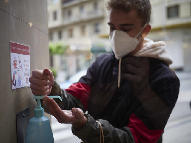A masked man disinfects his hands before entering a shop in Pamplona, Spain. (Getty Images)