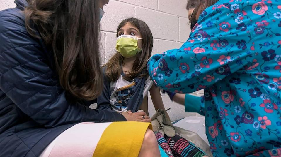 Alejandra Gerardo, 9, looks up to her mom, Dr. Susanna Naggie, as she gets the first of two Pfizer COVID-19 vaccinations during a clinical trial for children at Duke Health in Durham, North Carolina. In Kansas City, Children's Mercy is leading the regional effort for the Pfizer trials.