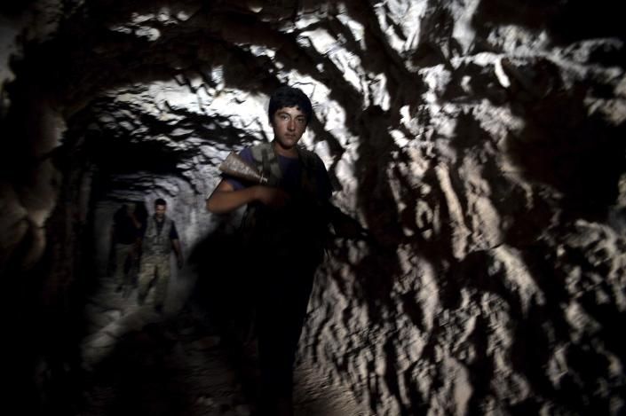 FILE -- In this Sunday, Sept. 9, 2018 file photo, fighters with the Free Syrian army leave a cave where they live, in the outskirts of the northern town of Jisr al-Shughur, Syria, west of the city of Idlib. Turkey and Russia appear to have succeeded in creating a demilitarized zone along the frontlines of Syria's flashpoint Idlib region, after rebels and an al-Qaida-linked alliance pulled back their heavy weaponry in accordance with the agreement. (Ugur Can/DHA via AP, File)