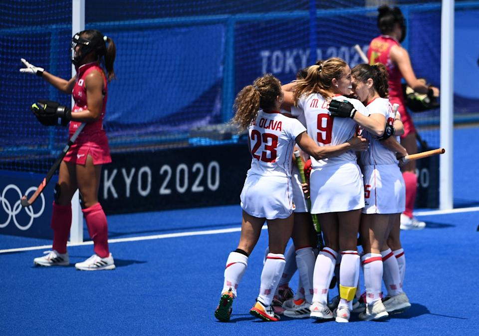 Spain's Candela Mejias (covered) celebrates with teammates after scoring against Japan during their women's pool B match of the Tokyo 2020 Olympic Games field hockey competition, at the Oi Hockey Stadium in Tokyo on July 31, 2021. (Photo by MARTIN BUREAU / AFP) (Photo by MARTIN BUREAU/AFP via Getty Images)