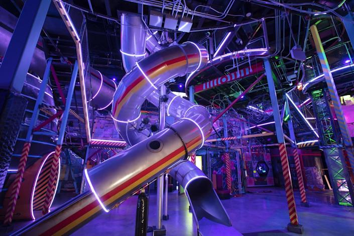A twisting indoor slide surrounded by neon.