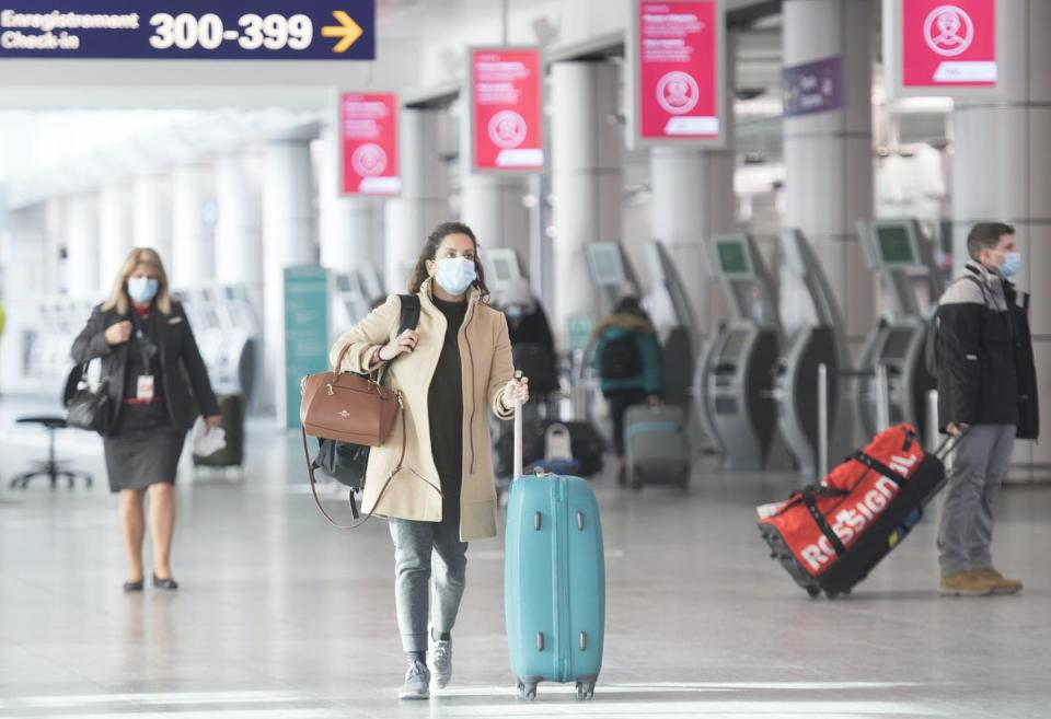 People in masks walk through an airport.