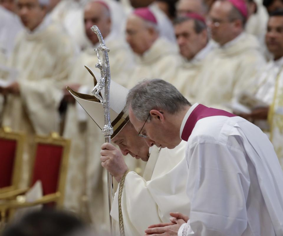 Pope Francis is flanked by Monsignor Guido Marini during a Chrism Mass inside St. Peter's Basilica, at the Vatican, Thursday, April 18, 2019. During the Mass the Pontiff blesses a token amount of oil that will be used to administer the sacraments for the year. (AP Photo/Alessandra Tarantino)