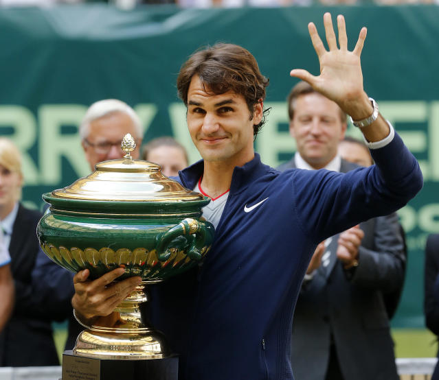 Switzerland's Roger Federer holds the trophy and waves after winning the final of the Gerry Weber Open tennis tournament in Halle, Germany, Sunday, June 15, 2014. Federer beat Colombia's Alejandro Falla 7-6 and 7-6. (AP Photo/Michael Probst)