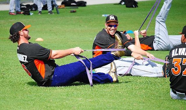 Miami Marlins catcher Jarrod Saltalamacchia, left, raided teammate Jose Fernandez's, right, locker and decided to wear Fernandez's jersey, purple jeans and gold high top sneakers to the Marlins morning stretch during a spring training baseball workout, Friday, March 7, 2014, in Jupiter, Fla. (AP Photo/Chuch King)