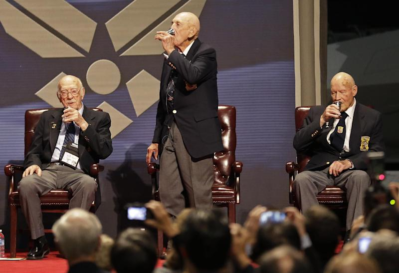 Richard Cole, center, proposes a toast with two other surviving members of the 1942 Tokyo raid led by Lt. Col. Jimmy Doolittle, Edward Saylor, left, and David Thatcher, Saturday, Nov. 9, 2013, at the National Museum for the US Air Force in Dayton, Ohio. The fourth surviving member, Robert Hite, was unable to travel to the ceremonies. (AP Photo/Al Behrman)