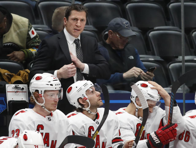 FILE - In this Dec. 19, 2019, file photo, Carolina Hurricanes coach Rod Brind'Amour stands behind players during the second period of an NHL hockey game against the Colorado Avalanche in Denver. The Hurricanes are determined to make a second straight deep run in the Stanley Cup playoffs. That can only happen if they do something they have rarely done over the past decade: defeat the New York Rangers. (AP Photo/David Zalubowski, File)