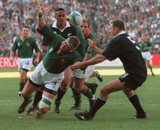 Springbok Kobus Wiese (C) loses the ball as he falls between All Blacks Jonah Lomu (behind) and Robin Brooke (R) during the 1995 Rugby World Cup final  in Johannesburg