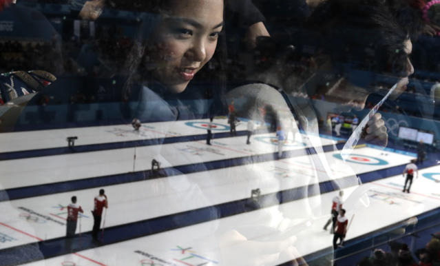 <p>A woman is seen behind a glass as she looks at men's curling matches at the 2018 Winter Olympics in Gangneung, South Korea, Sunday, Feb. 18, 2018. (AP Photo/Natacha Pisarenko) </p>