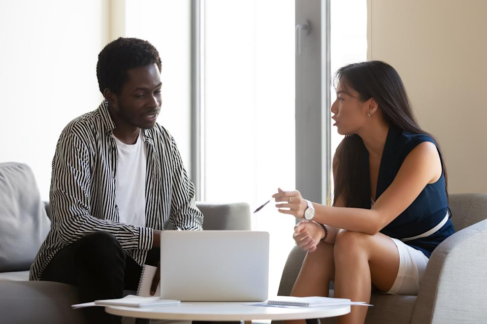 Asian ethnicity female bank counsellor consulting american man, client and representative sitting indoors talking, banker provides helpful information about lease receiving, banking services concept