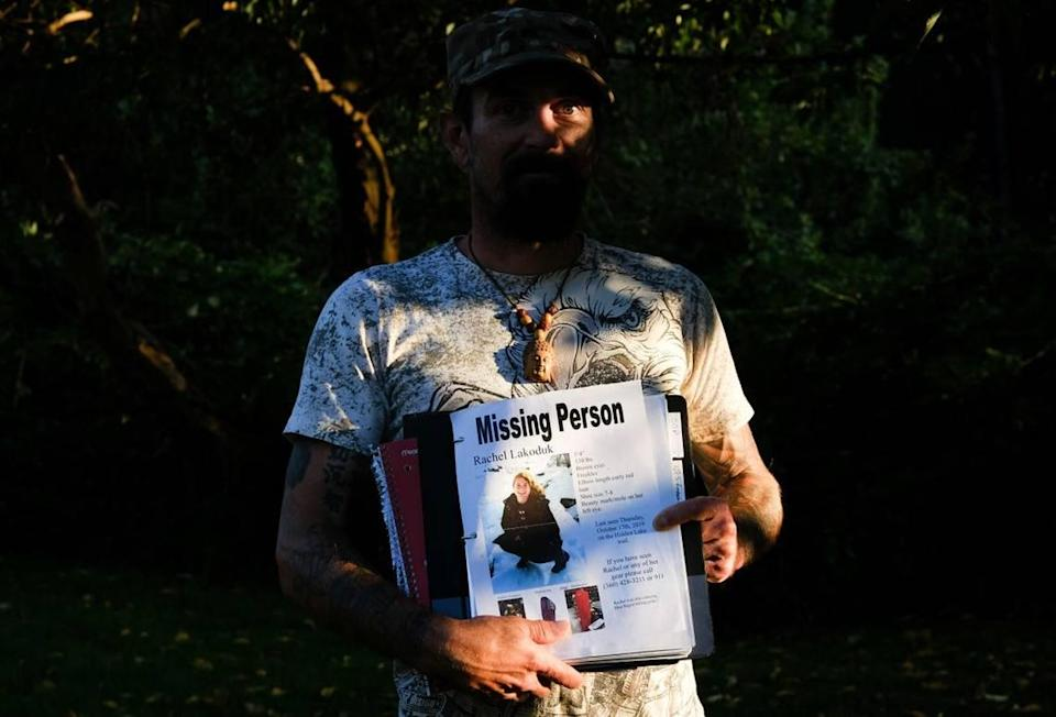 """Carlton """"Bud"""" Carr Jr. poses for a photo on Monday, Aug. 23, 2021, in the backyard of his home in Concrete, Wash. Carr is holding the file containing his search notes on Rachel Lakoduk, a 28-year-old Moses Lake hiker who went missing on Oct. 17, 2019, while attempting to reach Hidden Lake Lookout – a remote fire lookout in the Mt. Baker-Snoqualmie National Forest. Carr owns and operates 49th Parallel, a private search and rescue group, and spent at least 70 days searching for Rachel."""