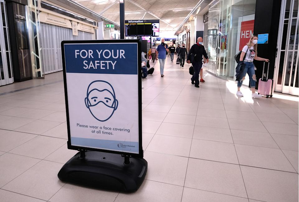 A sign telling travellers to wear face covering for their safety is displayed at Stansted Airport, Essex.. Picture date: Monday July 13, 2020.