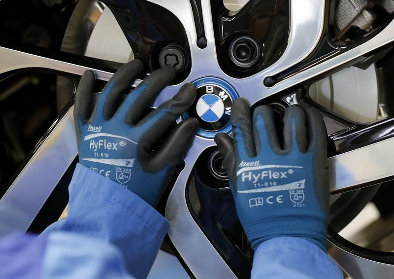 A worker mounts the logo on a rim at the serial production BMW i3 electric car in the BMW factory in Leipzig