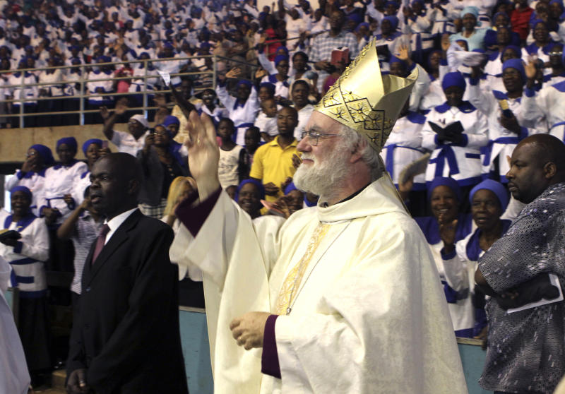 """FILE- Britain's Archbishop of Canterbury Rowan Williams greets worshippers to a religious service in Harare, Zimbabwe, in this file photo dated Sunday, Oct. 9, 2011. In an interview published Saturday Sept. 8, 2012, in Britain's Daily Telegraph newspaper, Williams said the Anglican Church is planning to give some of the global duties of the Archbishop of Canterbury to a """"presidential"""" figure so the archbishop can concentrate on leading the Church of England, and admitted he didn't do enough to prevent divisions in the Anglican church over homosexuality. (AP Photo/Tsvangirayi Mukwazhi, File)"""