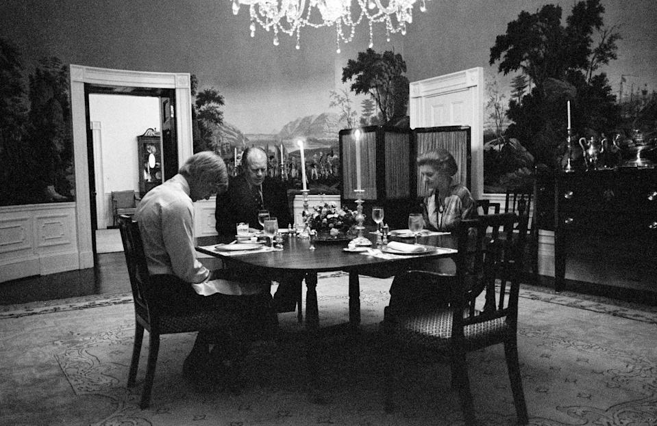 <p>President Gerald R. Ford, First Lady Betty Ford, and their son, Steven Ford, say grace prior to eating dinner in the President's dining room on the second floor of the White House Executive Residence on August 20, 1974.</p>
