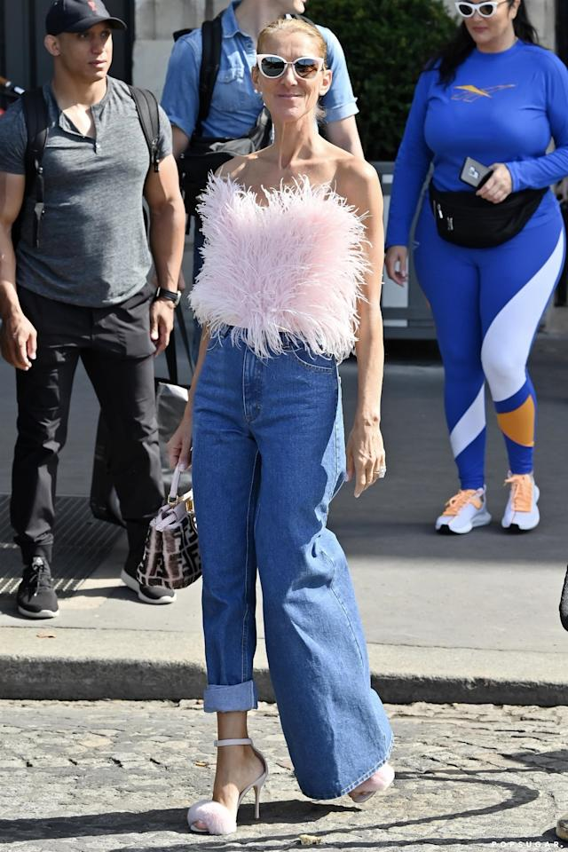 <p>Celine amped up her outfit with a feather pink top, furry sandals, and a monogrammed Fendi bag.</p>