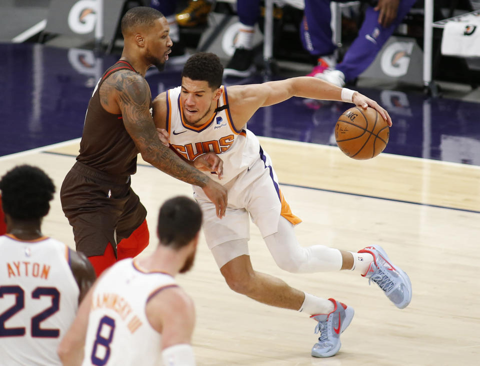 Phoenix Suns' Devin Booker muscles his way towards the basket against Portland Trail Blazers' Damien Lillard during the first half of an NBA basketball game Monday, Feb. 22, 2021, in Phoenix. (AP Photo/Darryl Webb)